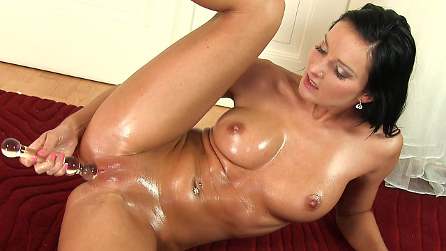 Oiled brunette charmer Niky Peach fuck glass sextoy from behind